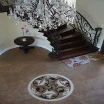 Chandelier overlooking radius staircase front entry