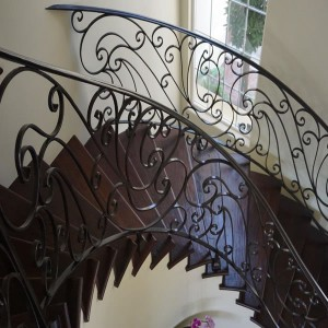 Mediterranean radius staircase with wrought iron balusters by custom home builders in Carlsbad CA