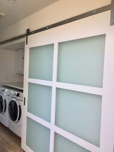 Modern contemporary laundry room with glass barn door